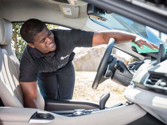 Spiffy technician interior detail and dashboard wipedown of sedan