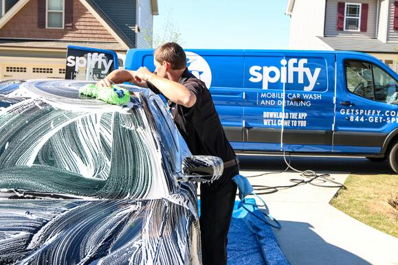 Spiffy technician washing car on-demand at home location