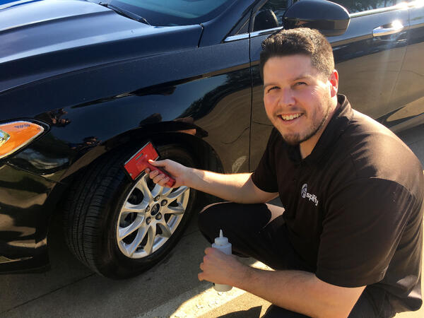 Paul showing off his smile while applying tire shine