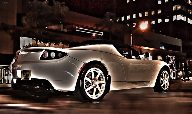 A like-new Tesla electric-powered luxury car driving in the city