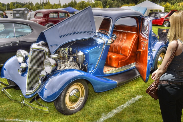 An unique antique car with orange leather seats and a metallic blue body