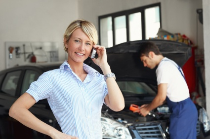 A multi tasking woman, conducting her work, while her car gets repaired at the auto shop