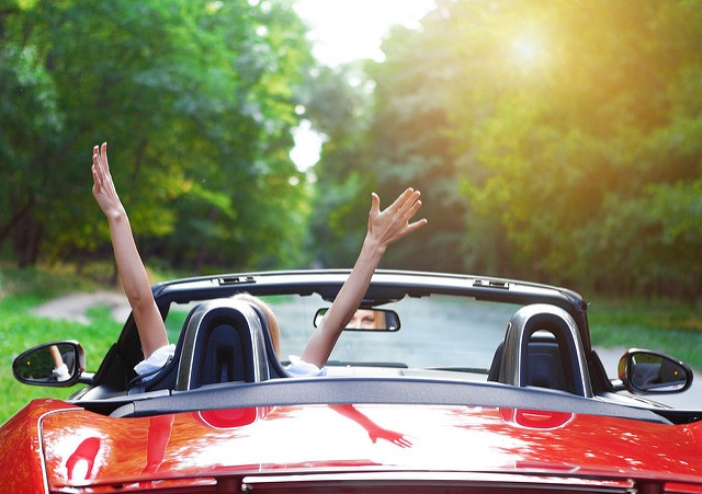 Independent woman lifting her arms excitedly in a red convertible