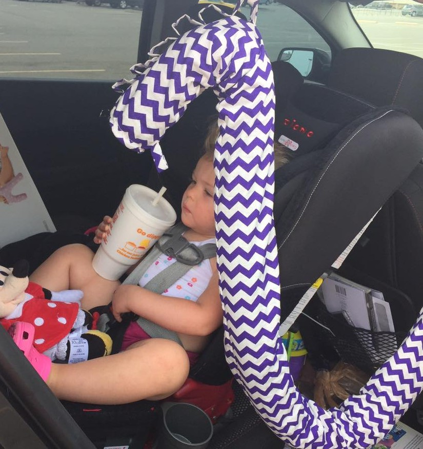 A toddler drinking a soda in a car seat