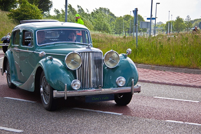 Couple riding in classic car shown cruising on the road