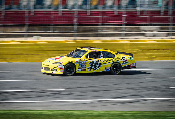 Charlotte Motor Speedway yellow car racing on track